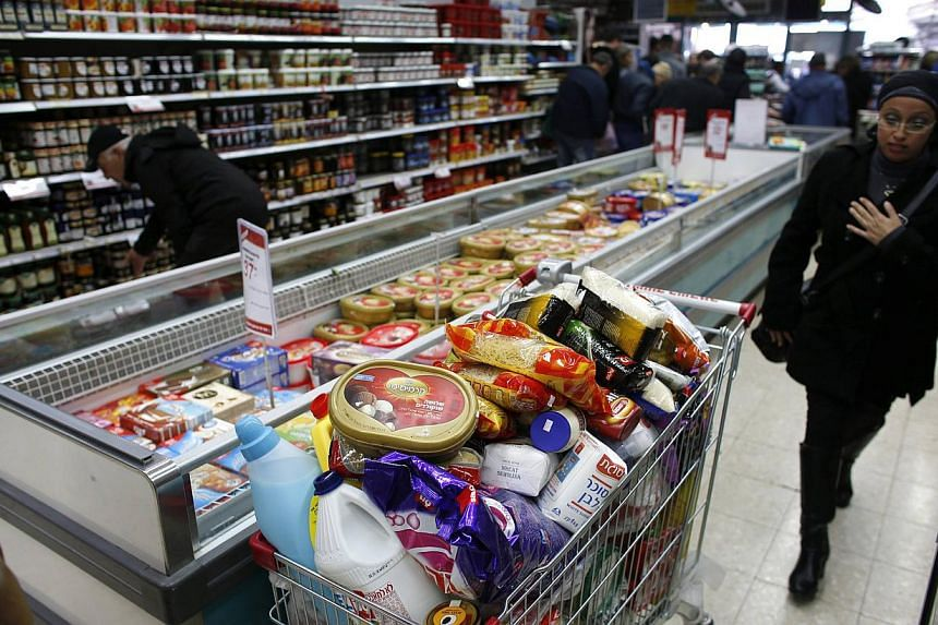 A woman walking near a shopping trolley full of products in a supermarket in Jerusalem, Israel, on Jan 6, 2015. Researchersfound 15 chemicals that were significantly associated with earlier menopause and declines in ovarian function, Some of wh