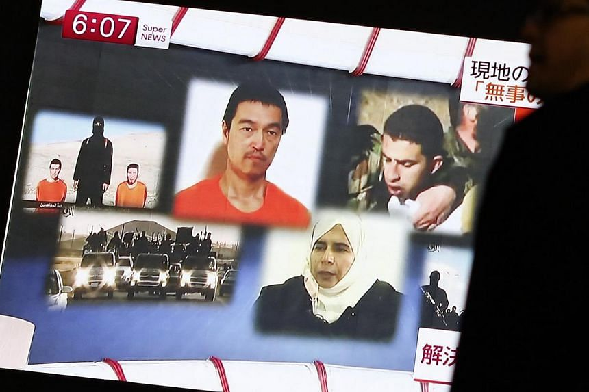 A man walking past a TV screen broadcasting a news programme about ISIS hostages Muath al-Kasaesbeh (top right), aJordanian air force pilot,and Japanese journalist Kenji Goto (top centre), in a street in Tokyo on Jan 29, 2015. -- PHOTO: R