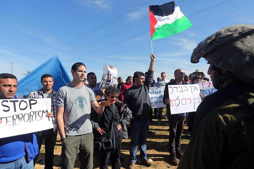 Palestinians and foreign activists during a protest near the Jewish settlement of Efrat in the Gush Etzion bloc in the West Bank, near Bethlehem on Jan 23, 2015. Israel on Friday published tenders to build 450 new settler homes in the occupied W
