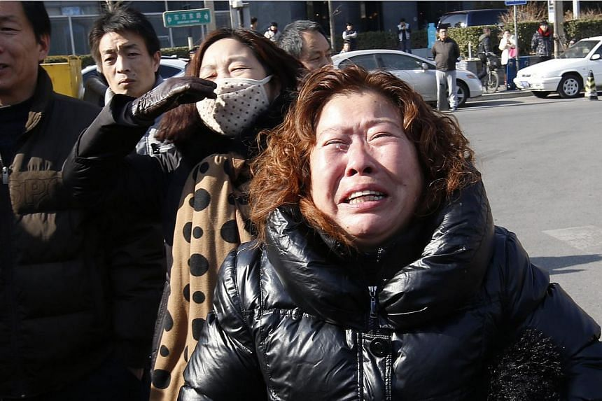 A family member of a passenger onboard the missing Malaysia Airlines flight MH370, cries during a protest demanding the Malaysian government to keep searching the missing flight, in front of the Malaysian Embassy in Beijing on Jan 29, 2015. -- PHOTO: