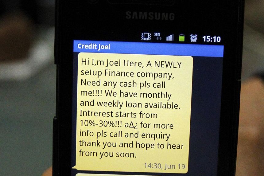 A text message of a loan scam shown on a mobile phone. -- PHOTO: LIANHE ZAOBAO