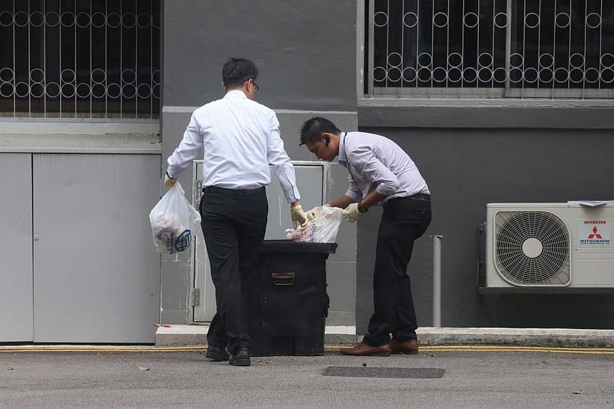 Police investigators looking through rubbish from a chute below a unit where the incident took place. -- ST PHOTO: SEAH KWANG PENG