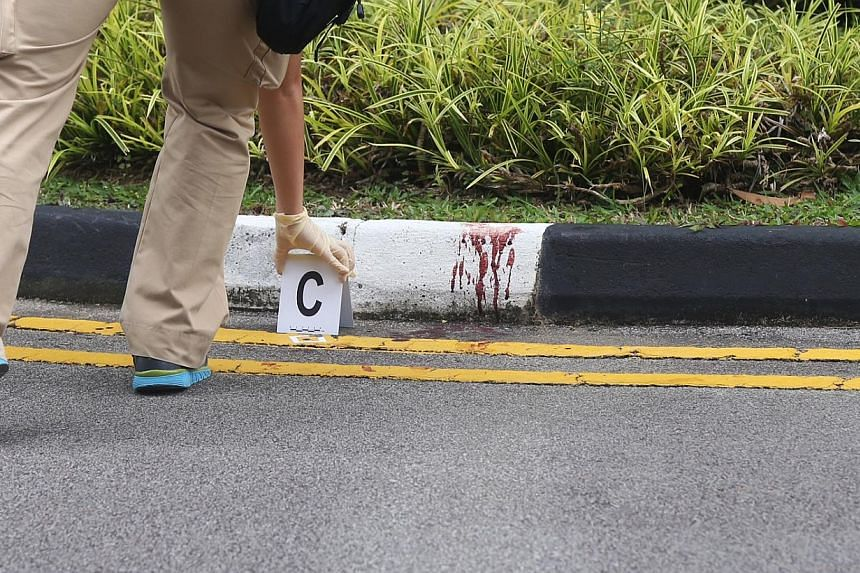 Police investigators placing markings near bloodstains at the carpark of Park View Mansions. -- ST PHOTO: SEAH KWANG PENG