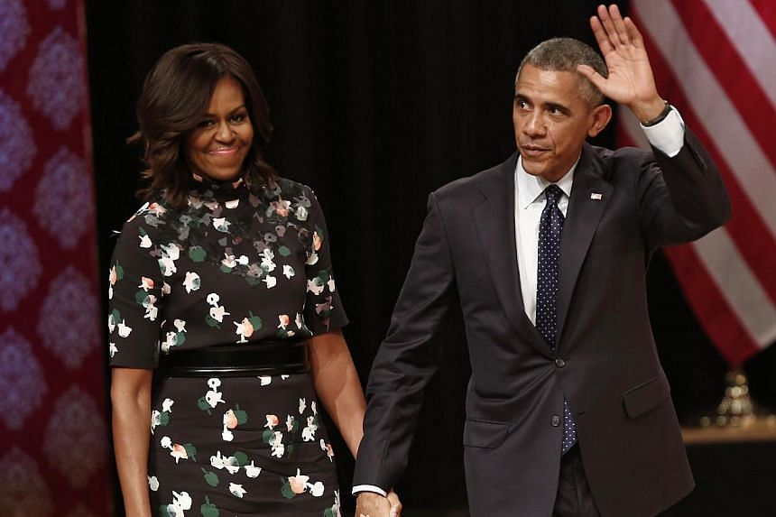 US President Barack Obama waves as he walks with first lady Michelle Obama to greet the audience after he delivered a speech at Siri Fort Auditorium in New Delhi on Jan 27, 2015. -- PHOTO: REUTERS