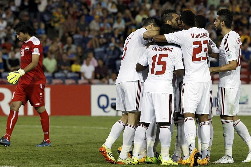 UAE's Ali Mabkhout (third left) celebrates his goal with team mates as Iraq's goalkeeper Mohammed Hameed Farhan (left) reacts during their Asian Cup third-place playoff soccer match at the Newcastle Stadium in Newcastle Jan 30, 2015. Ali Mabkhout put