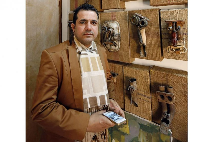 Iraqi artist Akeel Khreef standing in front of his art pieces depicting jihadists created on worn-out shoes on Jan 13, 2015 at his workshop in Baghdad. -- PHOTO: AFP