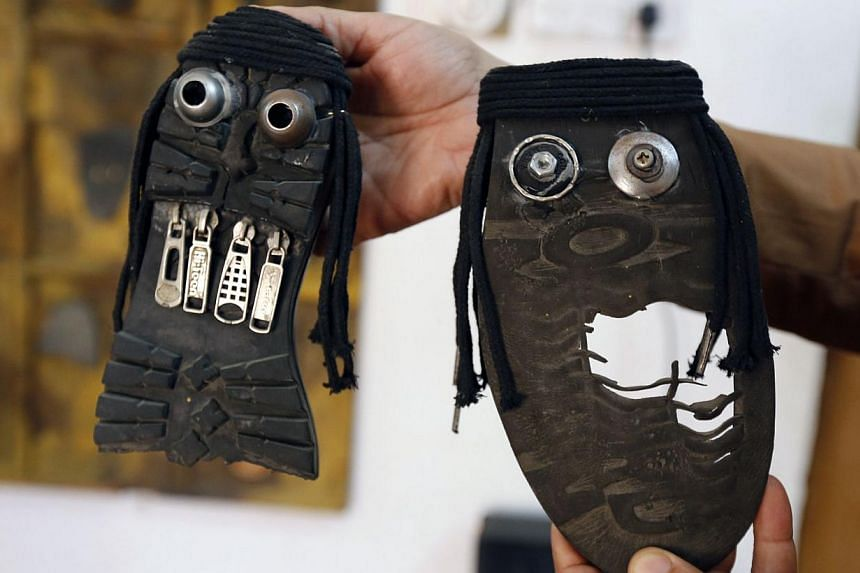 Iraqi artist Akeel Khreef showing some of his art pieces depicting jihadists on the soles of worn-out shoes on Jan 13, 2015 in Baghdad. -- PHOTO: AFP