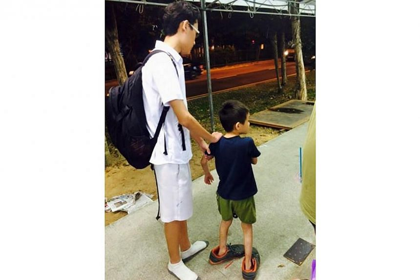 Facebook user Zen Ginji on Wednesday posted a photo of the boy in oversized shoes with a caption commending the student. He said the student is from Edgefield Secondary School in Punggol. -- PHOTO: ZEN GINJI/FACEBOOK