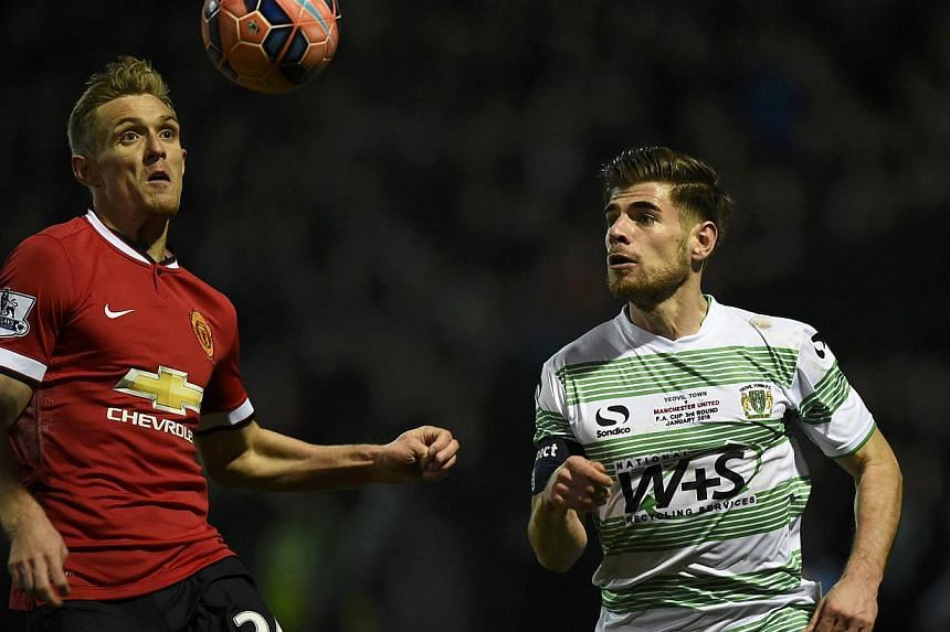 Darren Fletcher of Manchester United (left) and Joseph Edwards of Yeovil chase the ball during their FA Cup third round soccer match at Huish Park, Yeovil, western England, Jan 4, 2015. -- PHOTO: REUTERS