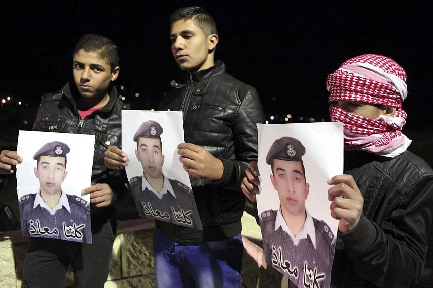 Relatives of Jordanian pilot Muath al-Kasaesbeh, who was captured by Islamic State after his plane crashed in northeastern Syria in December during a bombing mission against them, hold pictures of him at the family's headquarters in the city of Karak