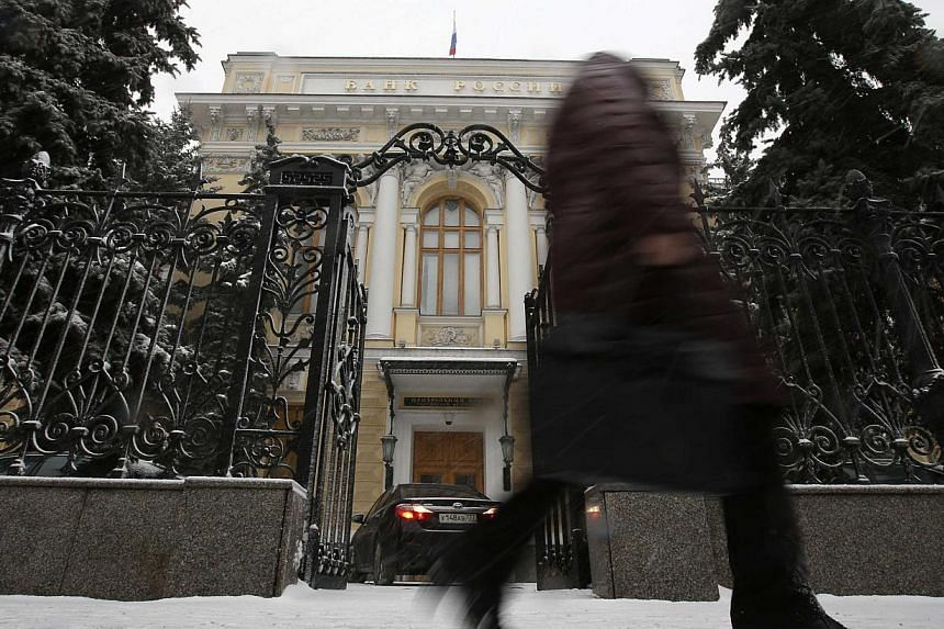 A pedestrian walks past the Central Bank headquarters in Moscow on Jan 30, 2015. Russia's central bank cut its key interest rate by two points to 15 percent on Friday, as the economy slides toward recession because of a collapse in global oil prices