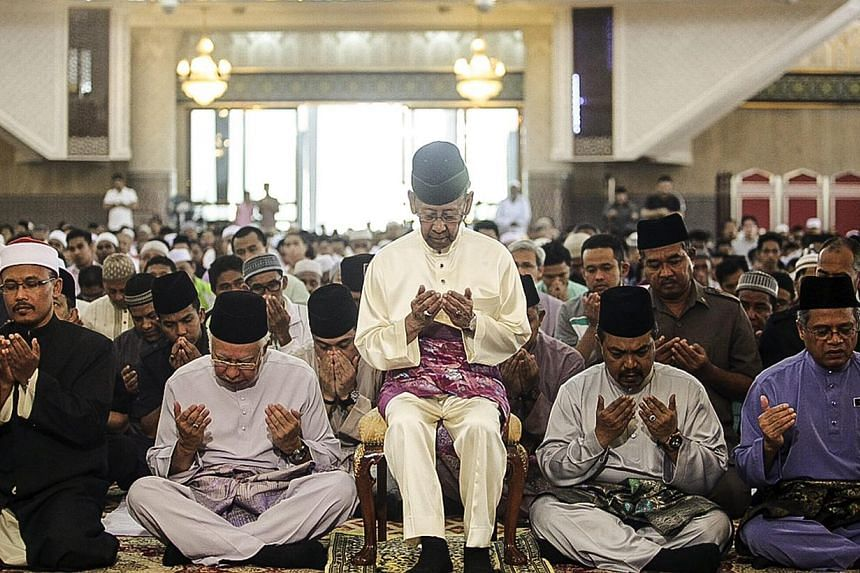 Malaysia's King Abdul Halim Mu'adzam Shah (centre) and Prime Minister Najib Razak (2nd from left), attend the special prayer to remembering the passengers and crews of MH370 Malaysian Airline missing plane at National mosque in Kuala Lumpur, Malaysia