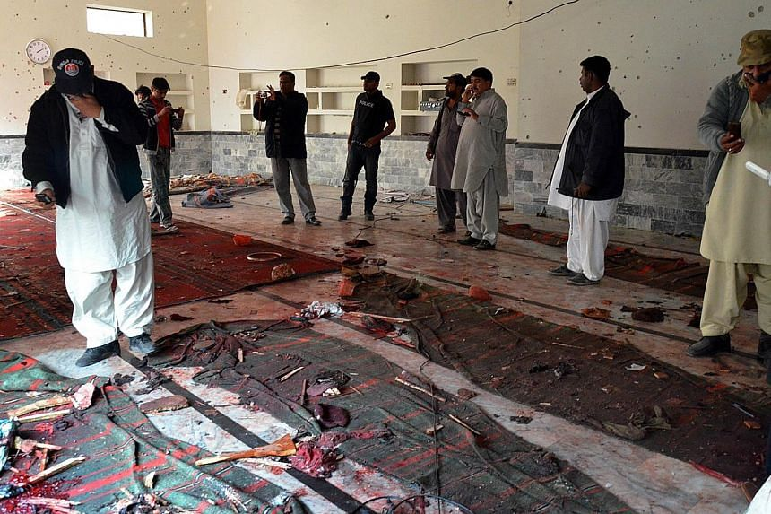 Pakistani security officials gather at a Shi'ite Muslim mosque after a bomb explosion in Shikarpur in Sindh province, around 470km north of Karachi on Jan 30, 2015. -- PHOTO: AFP