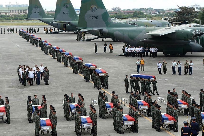 Philippine police commandos carrying the flag-draped coffins of their fallen comrades from C-130 planes shortly after arriving at a military base in Manila on Jan 29, 2015. -- PHOTO: AFP