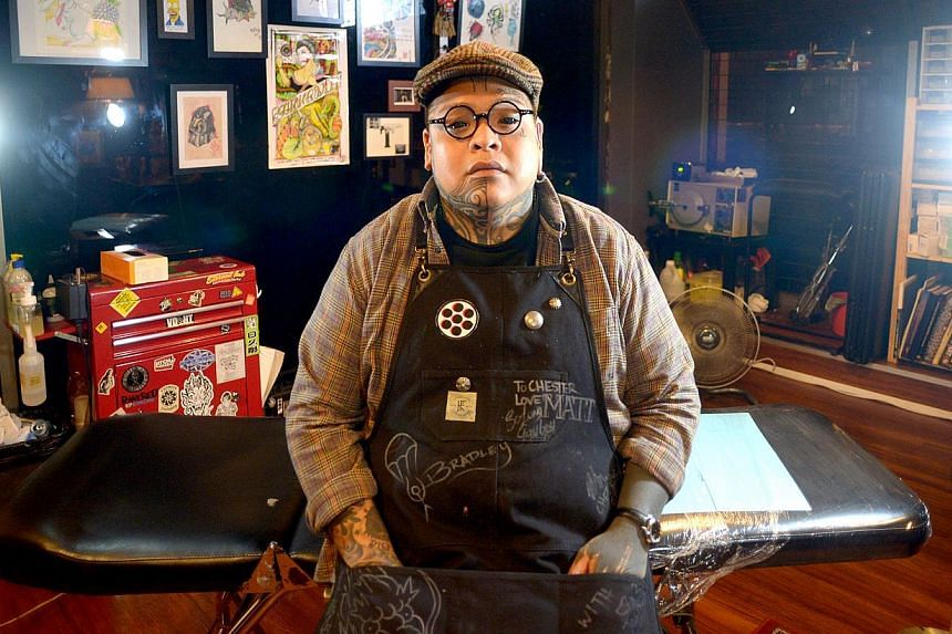 Tattoo artist Chester Lee, 28 has an eyeball tattoo done by American artist Luna Cobra. -- ST PHOTO: JAMIE KOH