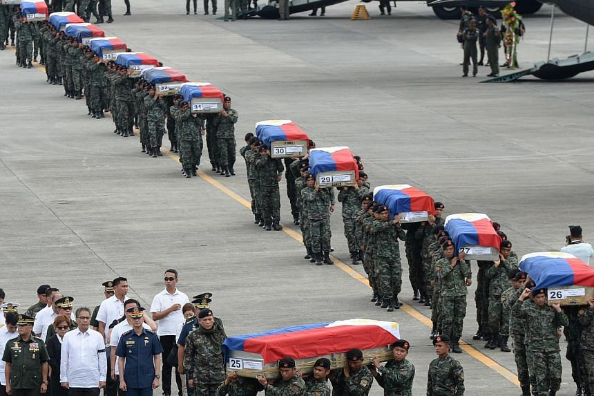 Philippine police commandos carrying the flag-draped coffins of their fallen comrades from C-130 planes shortly after arriving at a military base in Manila on Jan 29, 2015. As many as 44 commandos were killed. -- PHOTO: AFP