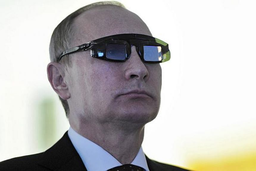 Russian President Vladimir Putin wears special glasses on a laboratory visit in St Petersburg, Russia on Jan 26 2015. One of Vladimir Putin's main opponents may have broken a taboo by publishing what he says is the pseudonym used by one the Russ