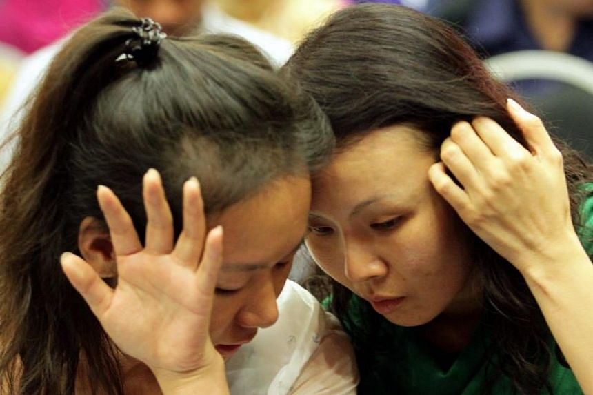 Relatives of a passenger on missing Flight MH370 at the DCA office in Putrajaya. -- PHOTO: THE STAR/ASIA NEWS NETWORK