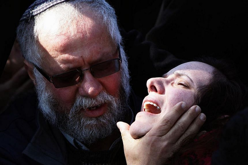 A man comforting Ms Tali Kalangel, the wife of 25-year-old Israeli army Captain Yochai Kalangel, during his funeral at the Mount Herzl military cemetery in Jerusalem on Jan 29, 2015. Capt Kalangel was one of two killed in a Hizbollah missile strike o