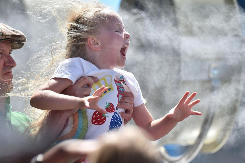 A child cooling off next to a fan at the 2015 Australian Open tennis tournament in Melbourne on Jan 19, 2015. PM Tony Abbott will unveil a new package of measures intended to improve childcare and support families in a speech on Feb 2, 2015, reported