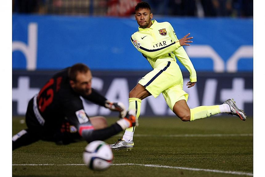 Barcelona's Neymar (right) scores past Atletico Madrid's goalkeeper Jan Oblak during their Spanish King's Cup quarterfinal second leg soccer match at Vicente Calderon stadium in Madrid on Jan 28, 2015.Barcelona boss Luis Enrique has leapt to th