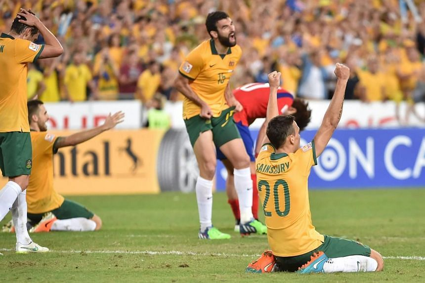 Australia's Trent Sainsbury (right) celebrates winning the AFC Asian Cup final football match against South Korea in Sydney on Jan 31, 2015. -- PHOTO: AFP