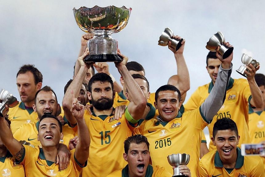 Australia's captain Mile Jedinak (centre) holds up the Asian Cup trophy as the team celebrates after winning their Asian Cup final football match against South Korea at the Stadium Australia in Sydney Jan 31, 2015. -- PHOTO: REUTERS