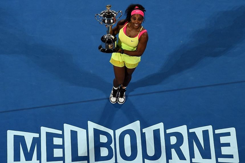 Serena Williams of the US poses with the trophy as she celebrates after victory in her women's singles final match against Russia's Maria Sharapova on day thirteen of the 2015 Australian Open tennis tournament in Melbourne on Jan 31, 2015. -- AFP