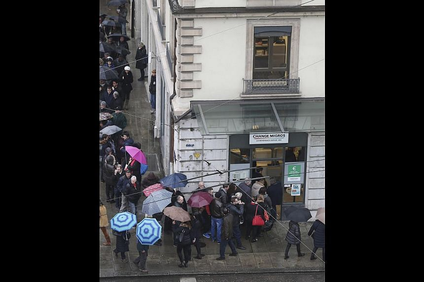 Thirteen days after the Swiss National Bank let the franc soar, the Monetary Authority of Singapore unexpectedly eased policy and allowed the Singapore dollar to weaken. (Right) People in Geneva queuing up to exchange their currency after their centr