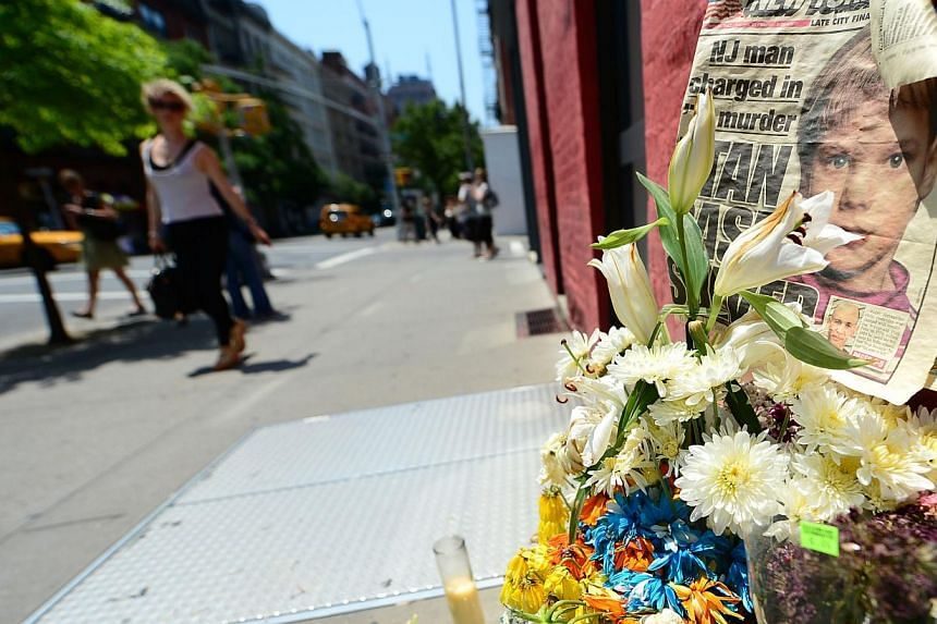 In this May 29, 2012 file photo, people walk past a street shrine to six-year-old Etan Patz, in front of the building where suspect Pedro Hernandez confessed to have strangled the boy in New York. -- PHOTO: AFP