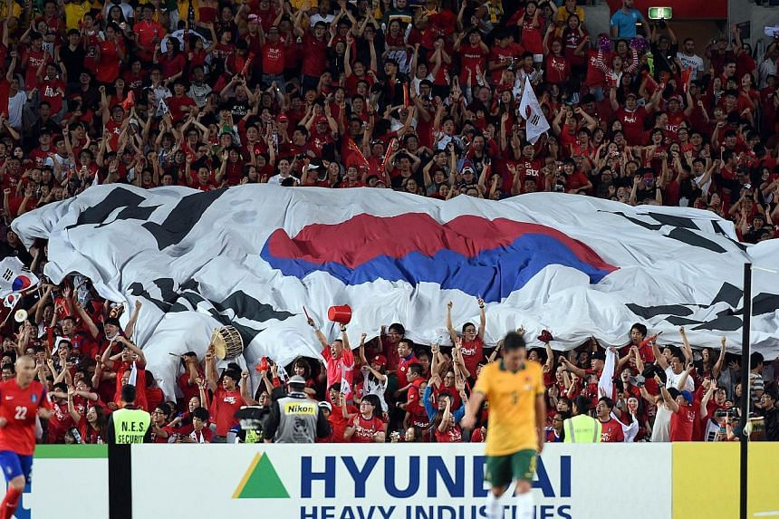 Spectators celebrate South Korea's last minute goal against Australia during the AFC Asian Cup football final between South Korea and Australia at Stadium Australia in Sydney on Jan 31, 2015. -- PHOTO: AFP