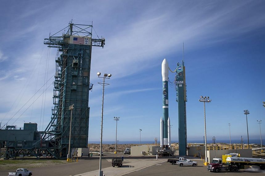 A handout picture made available by NASA on Jan 30, 2015 shows the United Launch Alliance Delta II rocket with the Soil Moisture Active Passive (SMAP) observatory onboard as the mobile service tower is moved back to help workers service the rocket at