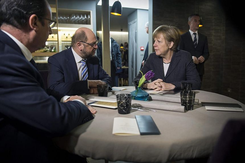 (From left) French President Francois Holland, President of the European Parliament Martin Schulz, and German Chancellor Angela Merkel talk during a meeting in Strasbourg, France, on Jan 30, 2015. -- PHOTO: EPA