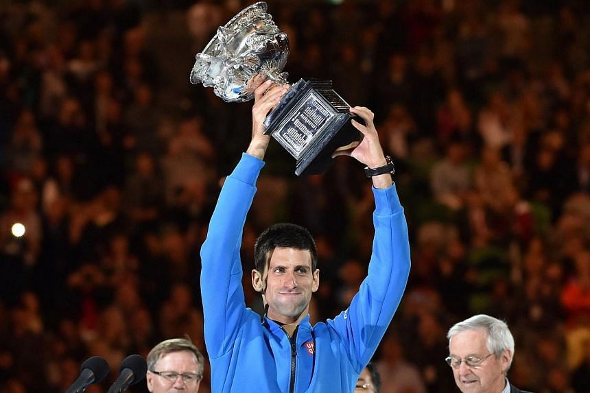 Novak Djokovic of Serbia (centre) holds up the winner's trophy at the awards ceremony as he celebrates his victory over Andy Murray of Britain in their men's singles final match on day 14 of the 2015 Australian Open tennis tournament in Melbourne on
