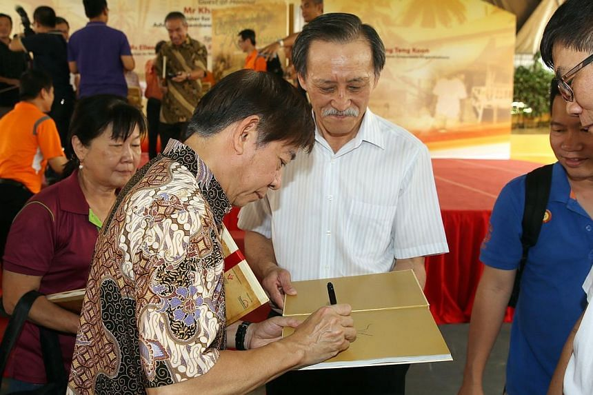 Minister Khaw signing his autograph on a copy of Chronicles of Remembrance for grassroot leaders and residents after the launch, including (centre) Ng Moi Song, 61, who is a resident featured in the book.-- ST PHOTO: SEAH KWANG PENG