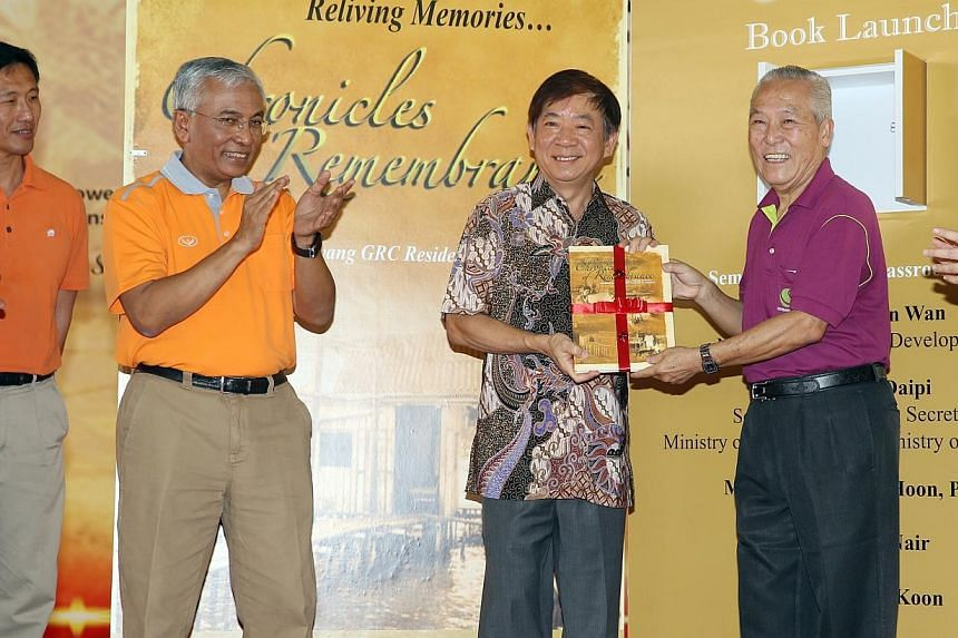 Law Shun Yong, organising chairman of the project, presenting the book Chronicles of Remembrance to Minister for National DevelopmentKhaw Boon Wan as Ong Ye Kung (left), and Sembawang GRC MP Hawazi Daipi (second from left) looks on.-- ST