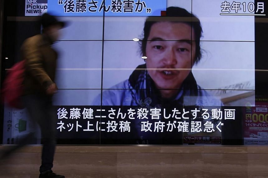 A pedestrian walks past television screens displaying a news programme about Japanese journalist Kenji Goto, who was a hostage of Islamic State in Iraq and Syria (ISIS) militants, on a street in Tokyo, on Feb 1, 2015. Singapore strongly condemns