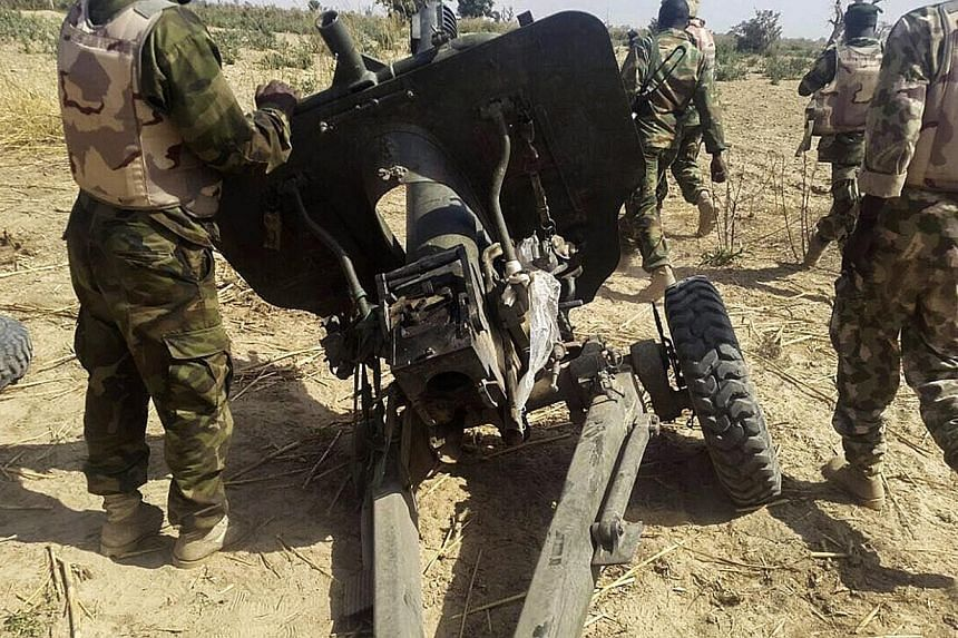 Nigerian soldiers walking near a captured field artillery piece that had been used by Boko Haram militants, in Maiduguri, in north-east Nigeria, on Jan 27, 2015. Boko Haram fighters on Sunday, Feb 1, launched a fresh attempt to take over the strategi