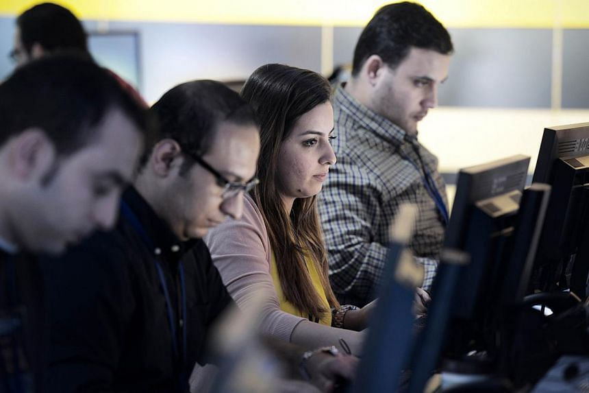 Alarab News Channel staff are seen on duty at the editorial office in the Bahraini capital Manama on Dec 15, 2014. -- PHOTO: AFP
