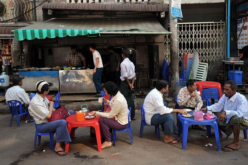Customers sitting with drinks at a traditional roadside coffee shop in downtown Yangon on Jan 28, 2015. -- PHOTO: AFP