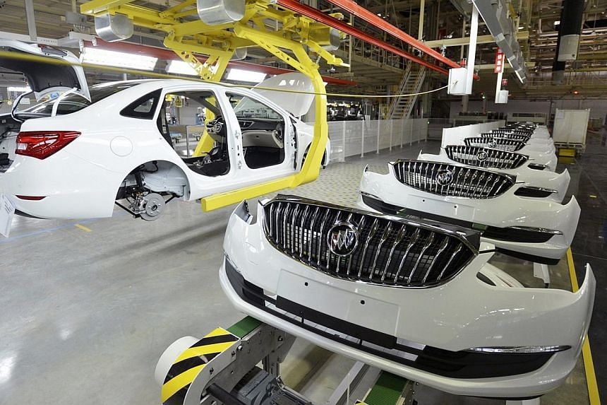An employee looks on next to an assembly production line of Buick cars at a General Motors factory in Wuhan, China. Activity in China's factory sector contracted in January for the first time in more than two years, an official survey showed. -- PHOT
