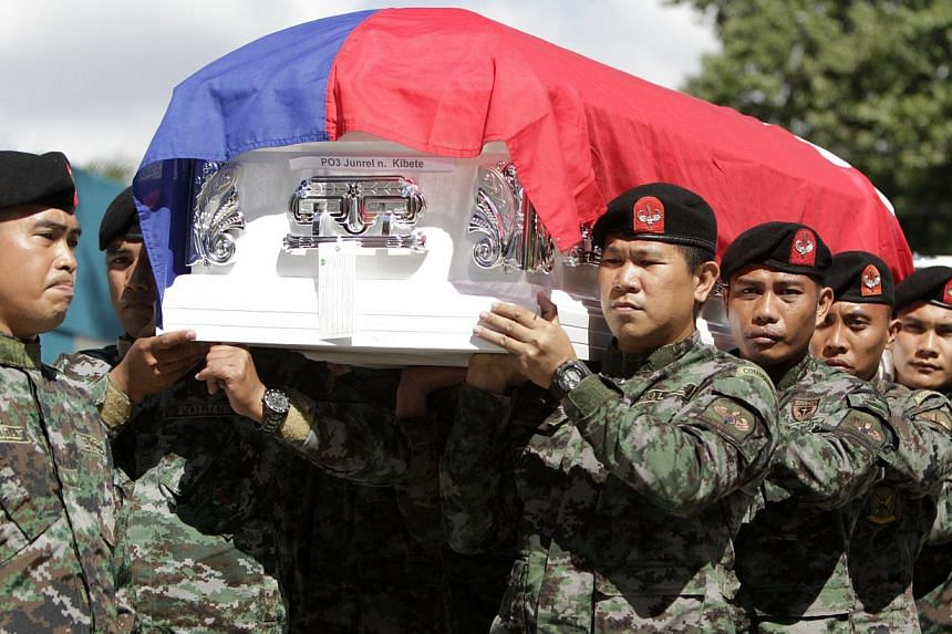 Members of the Philippines' = elite Police Special Action Force (SAF) carry one of the coffins of their forty-four comrades during the funeral at Camp Bagong Diwa in Taguig, south of Manila, Philippines on Jan 31, 2015. The Philippine interior m