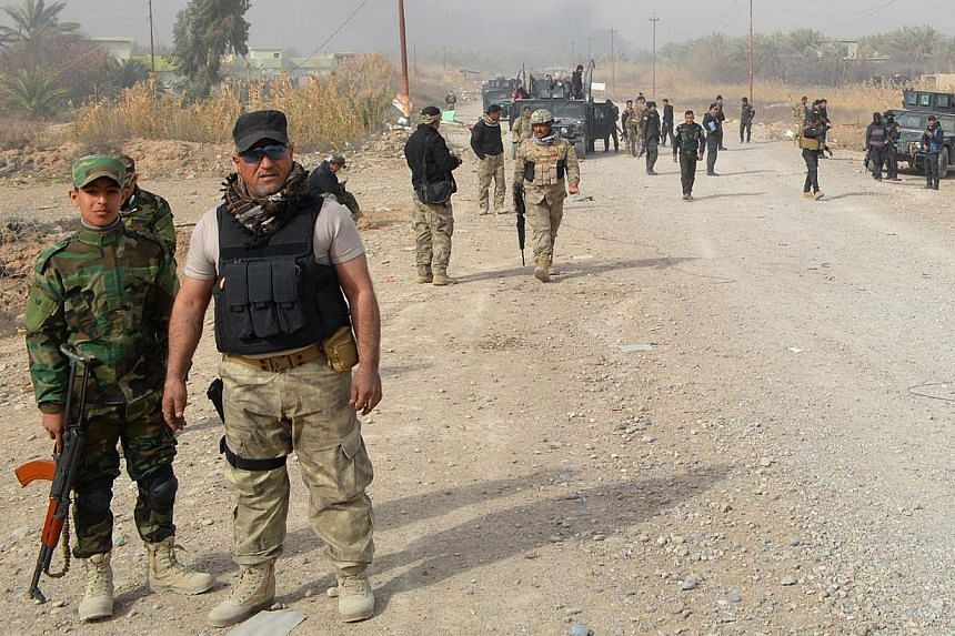 Iraqi government forces stand on a road after they claiming they gained complete control of Diyala province, north-east of Baghdad, from the Islamic State in Iraq and Syria (ISIS), on Jan 26, 2015.ISIS militants beheaded an Iraqi police officer
