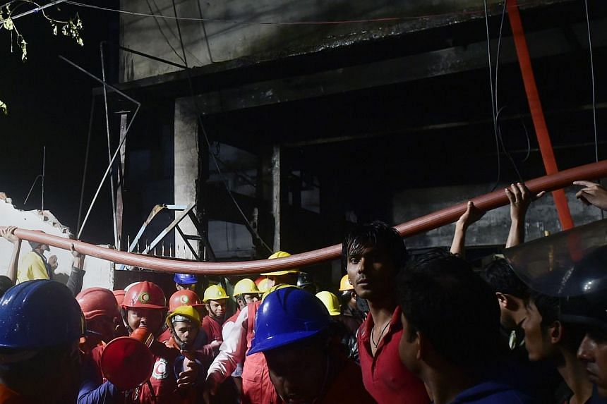 Bangladeshi volunteers and residents lift up a hosepipe as firefighters try to extinguish a fire in a plastic factory in Dhaka on Jan 31, 2015.Bangladesh on Sunday ordered an enquiry into a plastics factory fire that killed 13 workers, the late