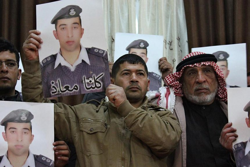 Relatives of Islamic State captive Jordanian pilot Muath al-Kasaesbeh hold his poster as they take part in a rally in his support at the family's headquarters in the city of Karak on Jan 31, 2015. -- PHOTO: REUTERS