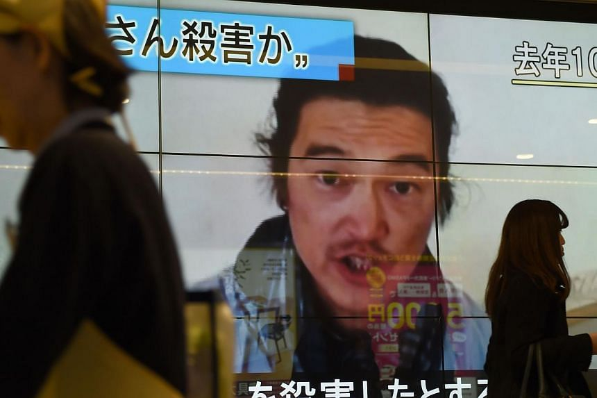 People walk past a big screen reporting that Japanese hostage Kenji Goto was killed by the Islamic State in Tokyo on Feb 1, 2015. -- PHOTO: AFP