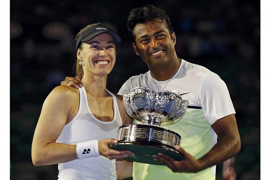 Martina Hingis (left) of Switzerland and Leander Paes of India pose with their trophy after defeating Kristina Mladenovic of France and Daniel Nestor of Canada to win their mixed doubles final match at the Australian Open 2015 tennis tournament in Me
