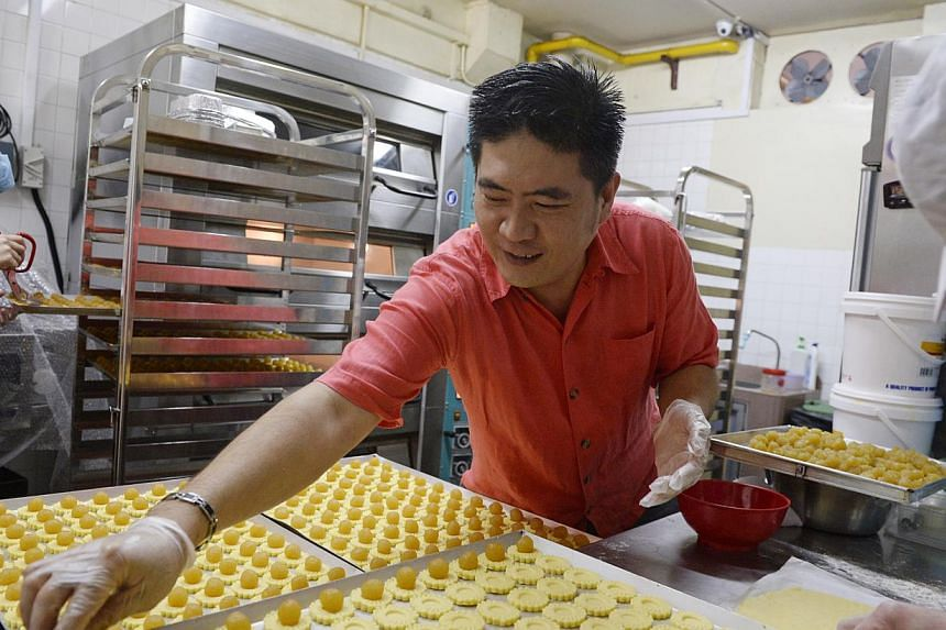 D'Pastry owner Patrick Koh and his team of about 10 people churn out 200 bottles of pineapple tarts a day, with a recipe only he and his wife know. -- ST PHOTO: MARK CHEONG