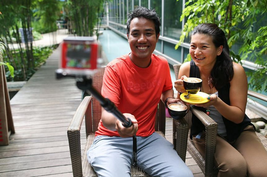 Fadzly Amir, 27 and Ruby Tan, 26, record their travels using a GoPro and then turn the footageinto video clips. --ST PHOTO: ONG WEE JIN