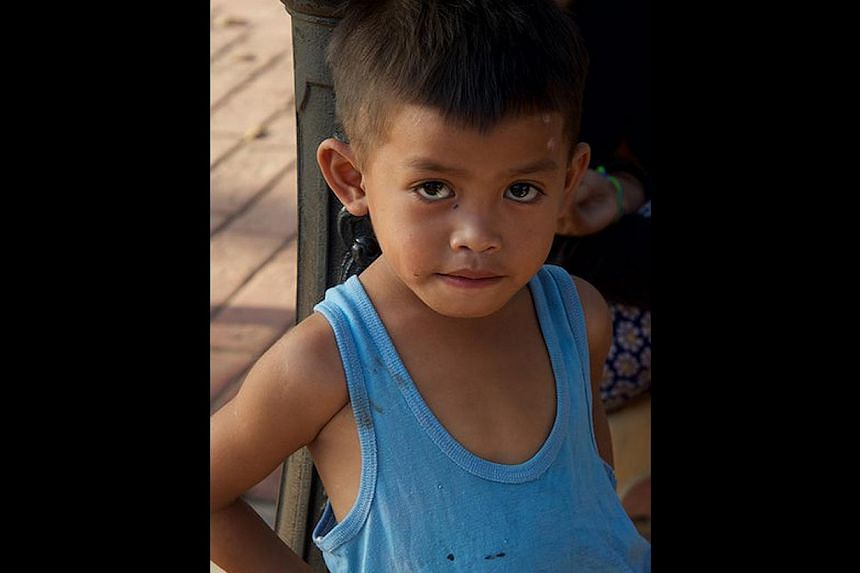 """""""Frederico"""", whose real identity is unknown, is seen lying naked on the floor, all skin and bones, with scabies and bruises all over his body, at the Manila RAC. Another boy was beaten to death there a year earlier. Street children watching TV from a"""